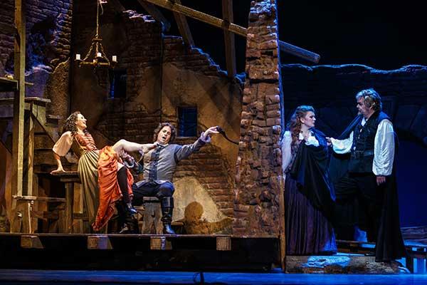 Rigoletto (Mark Delavan, right) comforts daughter Gilda (Lyubov Petrova, right) as eavesdrop on the amorous activities of the Duke and Maddalena (Michael Wade Lee and Samantha Korbey, left). PHOTO DAVID BACHMAN